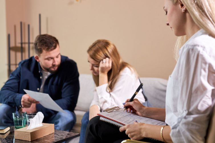 unhappy couple after therapy session with family psychologist, holding divorce document, alimony issue